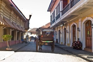 "The famous street with a ""caritela"" (horse-drawn carriage) passing by.."